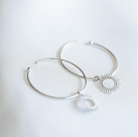 Boucles d'oreilles créoles en argent rhodié avec petits soleils pendants